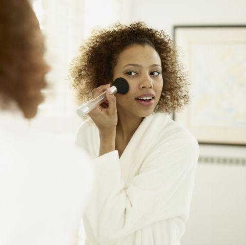 African woman applying makeup