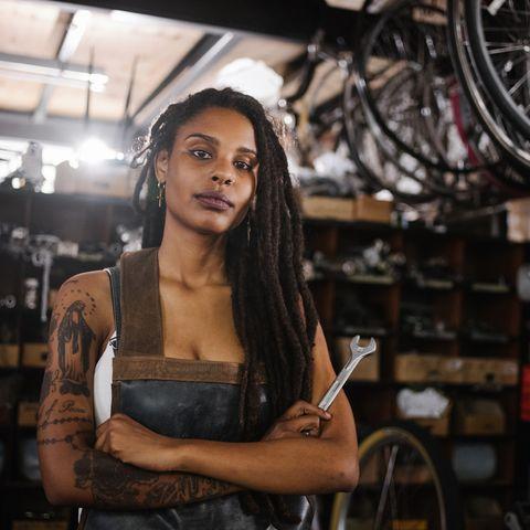 afro woman bicycle mechanic looking proud in bike repair worksho