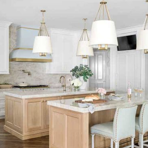 kitchen with retro stove hood, white shaded lights, marble counters