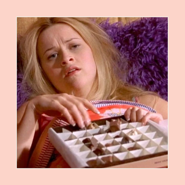 woman laying in bed with a box chocolates