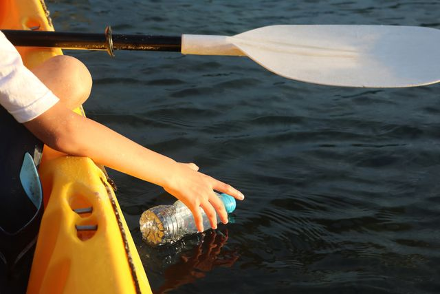 children are reaching for a bottle of plastic waste in the ocean while paddling a kayaking