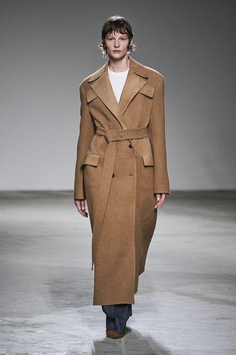 Fashion model, Fashion, Fashion show, Clothing, Runway, Overcoat, Coat, Outerwear, Trench coat, Beige,