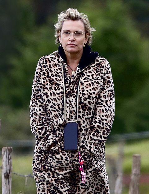 la soprano, con un abrigo de print animal y gafas de ver, paseo su perro en soledad