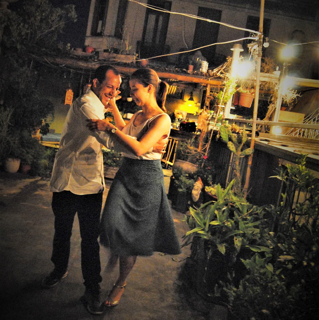 smiling man and woman in a gray skirt tangoing at night in an alley, beside potted plants and a deck