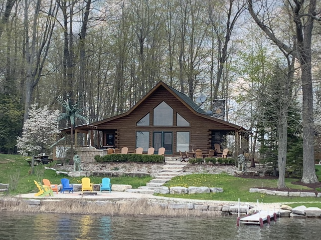 log cabin with colorful patio furniture in front of a lake