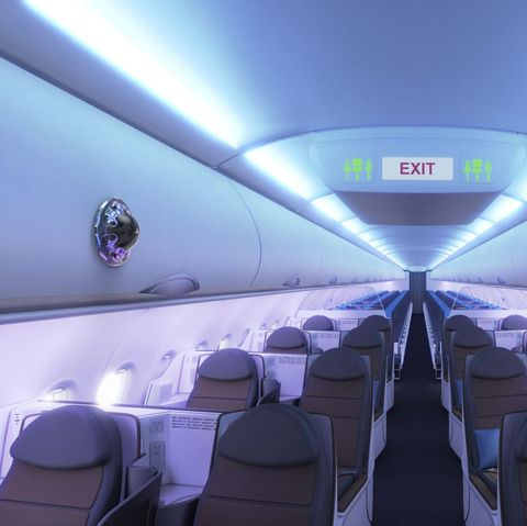 an empty airplane cabin with a device that looks like a video camera attached to one of the overhead compartments