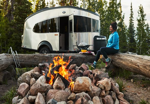 woman sitting near campfire and airstream mobile home