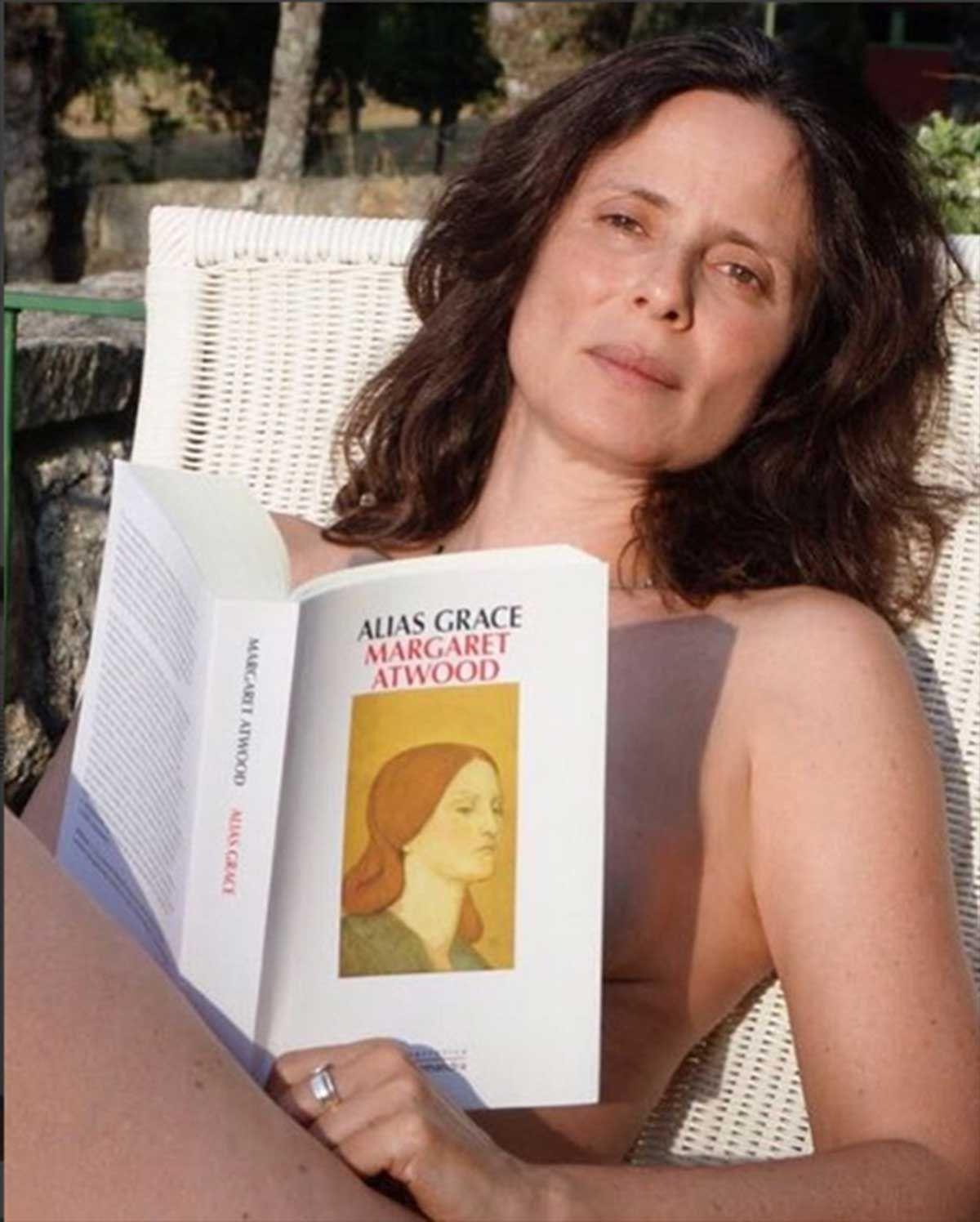 Aitana Sánchez-Gijón toma el soldesnuda tapándose con la obra 'Alias Grace' de Margaret Atwood