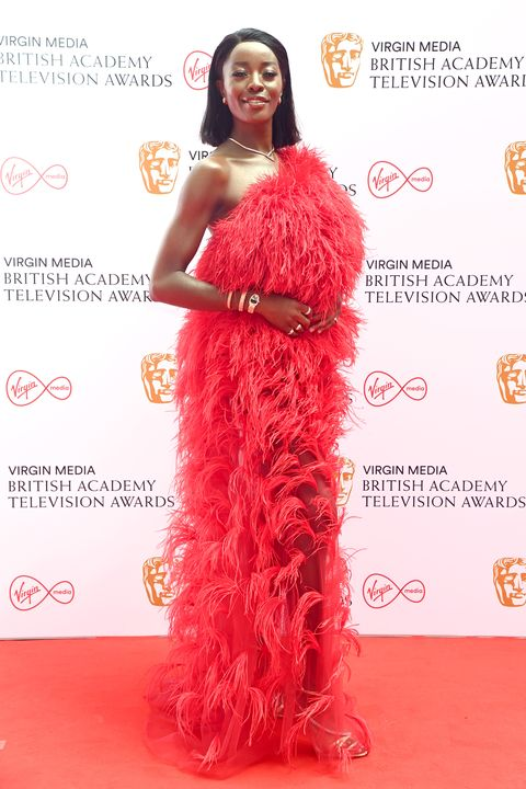 aj odudu wearing red feathering dress at the virgin media british academy television awards 2021