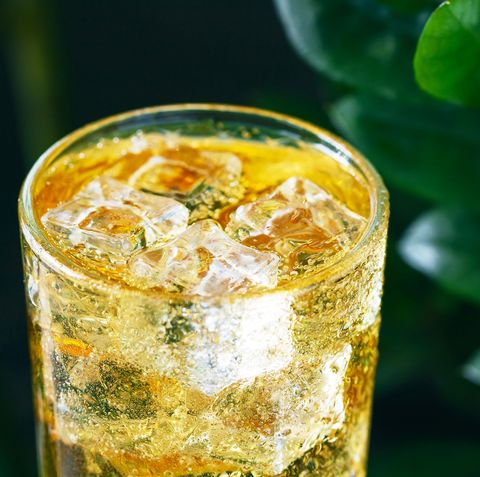 Close-up of a fresh yellow sparkling drink with ice in a highball glass against green nature backgrounds.