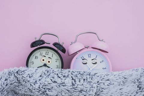 alarm clock female and male sleeping in bed