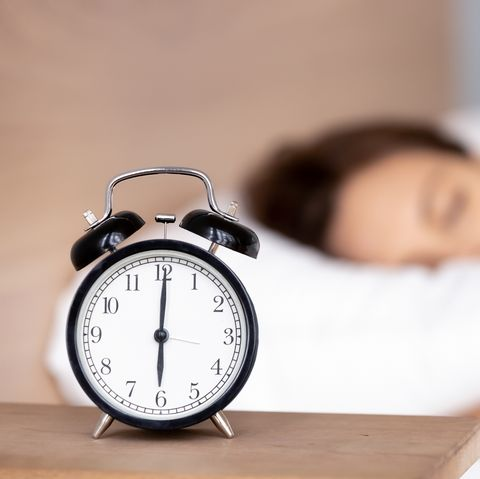 alarm clock on bedside table with woman sleeping on background