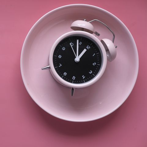 alarm clock on pink color plate on table