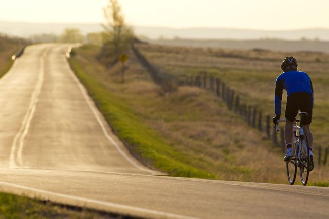 a male cyclist wearing a jacket and shorts, riding along a long undulating road in the early morning light