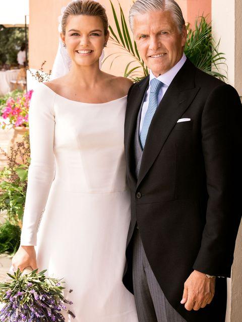 la hija del torero, vestida de novia, posa sonriente con su padre en su enlace