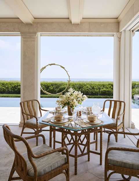 a small dining table with four chairs on a poolside terrace
