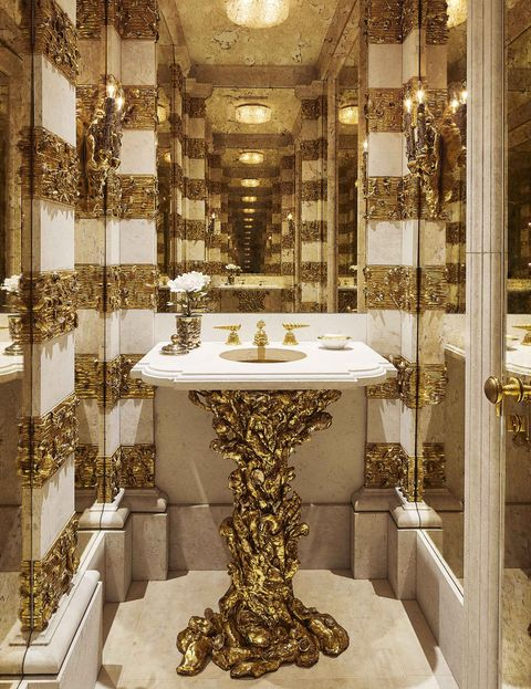 a powder room with white marble and gold details on the sink pedestal and walls