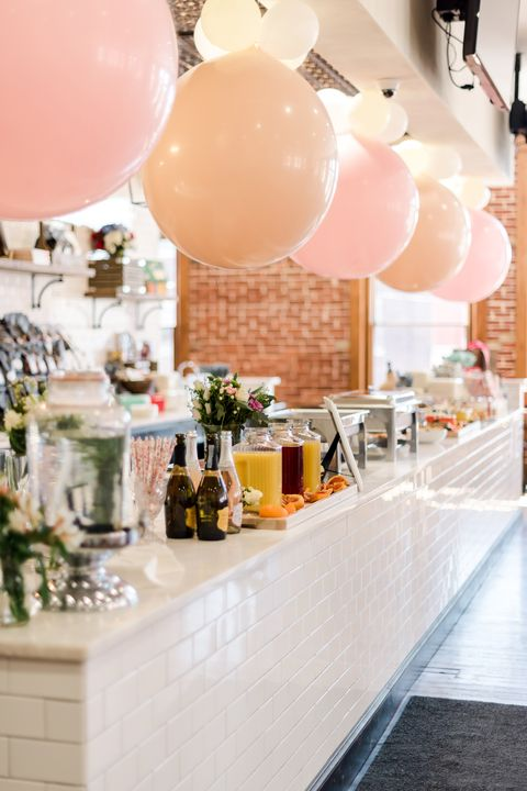 food is displayed next to a mimosa bar at alex drummond's wedding shower