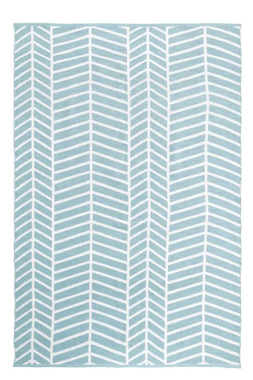 Alfombra de exterior azul con motivos decorativos blancos