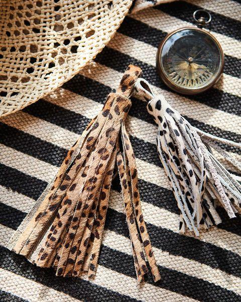 sombrero de paja, borlones con print leopardo y brújula decorativa