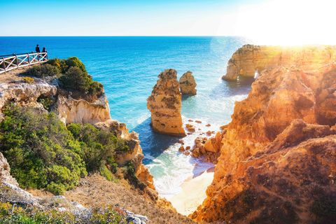 praia da marinha, one of the most beautiful beaches of portugal, algarve, was named by michelin guide to be one of the 10 most beautiful beaches in europethis photo captures the setting sun above one of the few natural arches near the beach
