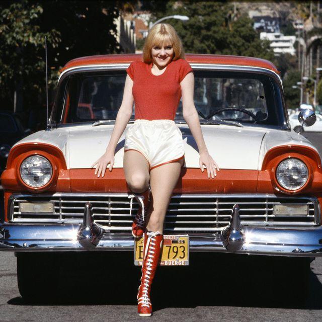 1970年代のアメリカ車の前でポーズを取る女優