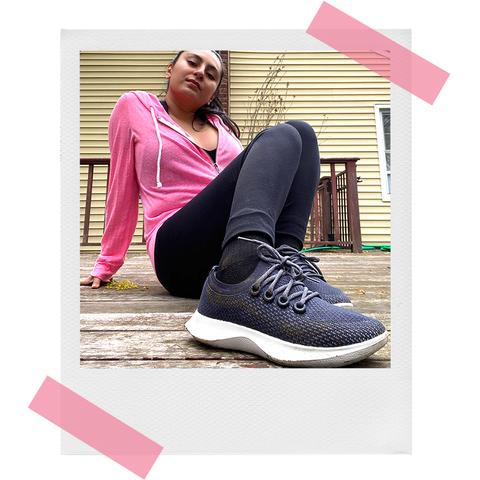 woman wearing pink hoodie showing off allbirds dasher sneakers outside