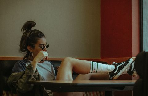 Leg, Sitting, Human leg, Room, Photography, Eyewear, Table, Black hair, Shoe, Fashion accessory,