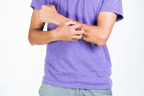 Midsection Of Man Scratching Hand While Standing Against White Background
