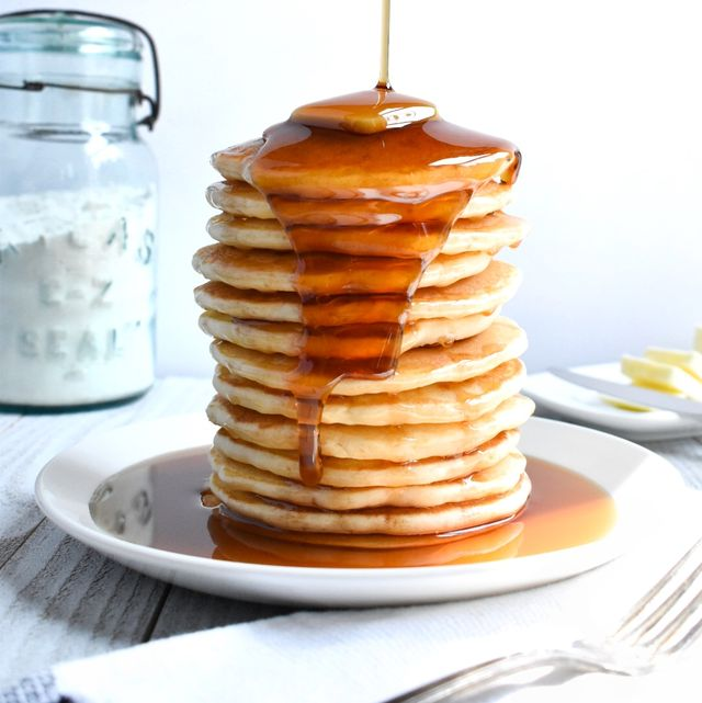 tall stack of pancakes with syrup being poured over them on a white plate alonside a fork, white napkin, a jar of flour and a dish of butter