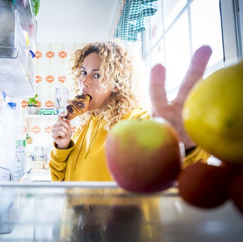 alternaive inside view of beautiful hungry adult woman eat tasty croissant with chocolate and open the fridge to take off some food    concept of coronavirus covid 19 lockdown quarantine people