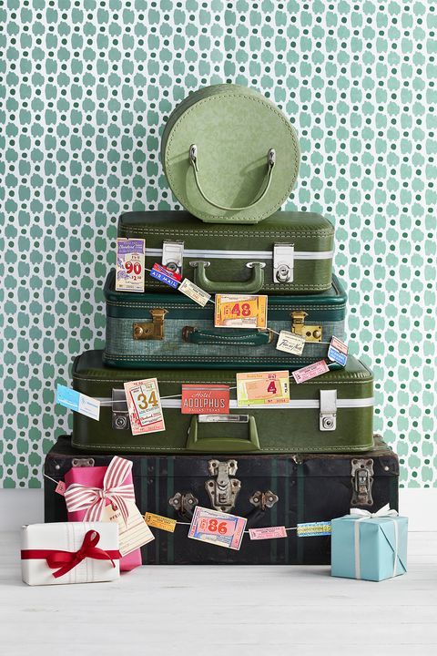 vintage luggage in shades of gree stacked in the shape of a christmas tree