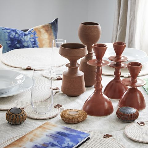 dining table set with place settings, glasses, terra vases, and glazed candlesticks