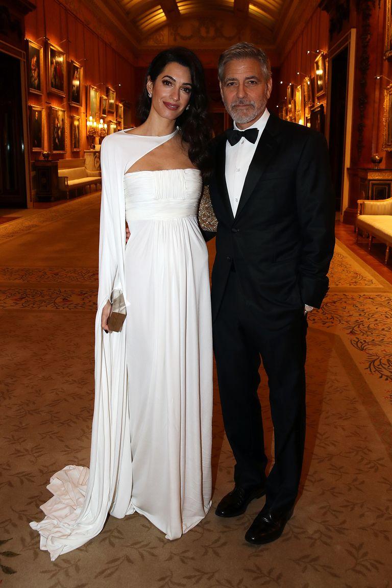 ee33542bc3 Amal Clooney elige un vestido capa blanco para su visita a Buckingham Palace