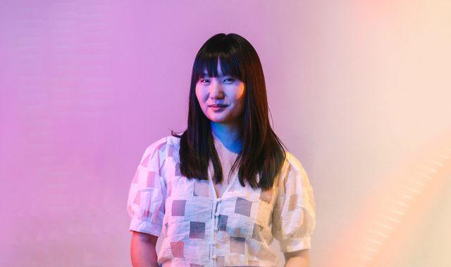 artist amanda phingbodhipakkiya poses against a pink and orange backdrop