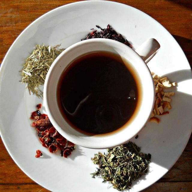 overhead view of cup of strong dark tea with piles of loose leaf tea in the saucer around it