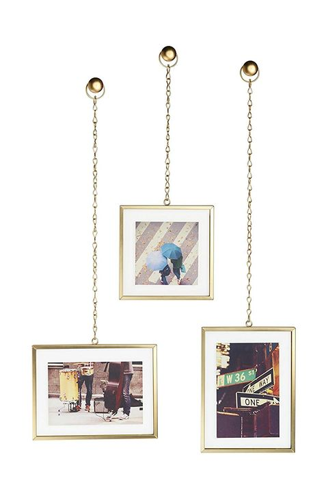 three gold frames hanging from chains