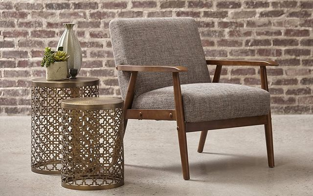 chair with wood frame next to two gold side tables