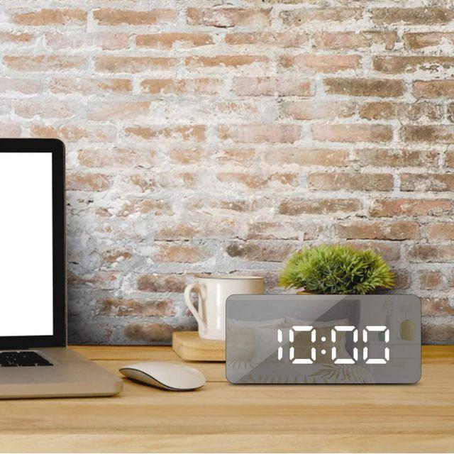 digital clock on desk next to jars on counter