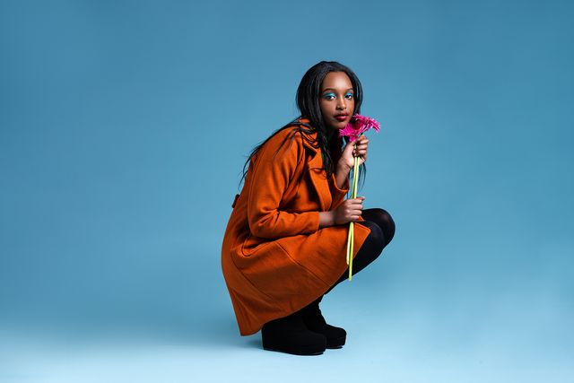 attractive young woman in orange trench coat holding a pink gerbera flower in front of blue background