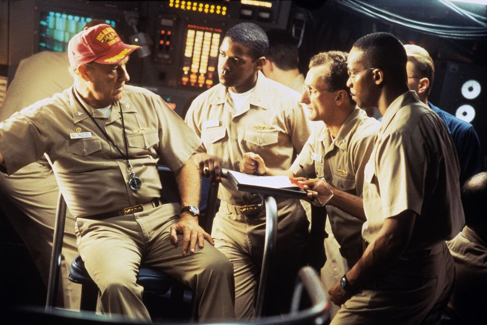 Crimson Tide (1995) Denzel Washington, Gene Hackman, Rocky Carroll, and Matt Craven sit inside a submarine set for Crimson Tide. Throughout the movie, they must decide whether to launch missiles at a Russian republic with nuclear warheads, or wait until the threat is clear.