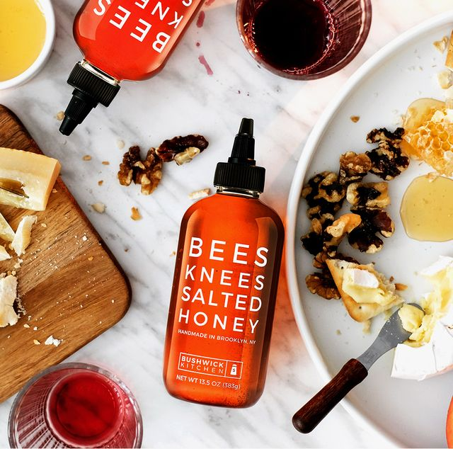bees knees salted honey on marble kitchen counter surrounded by charcuterie board of sausage cheese nuts peaches crackers and wine