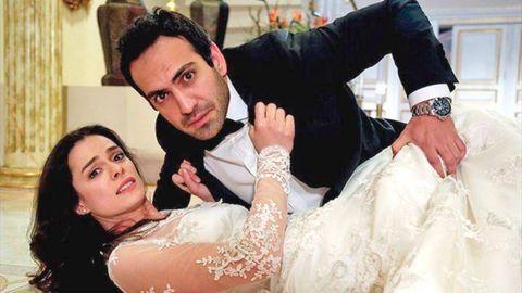 Özge Özpirinçci y bugra gülsoy, vestidos de novios, tirados en el suelo, miran a cámara en una escena de amor a segunda vista