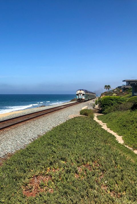 best train trips - Amtrak Pacific Surfliner train with blue ocean and blue sky