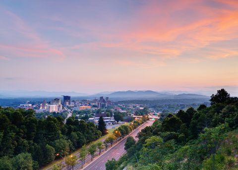 An aerial view of a road and skyline of Asheville at dusk