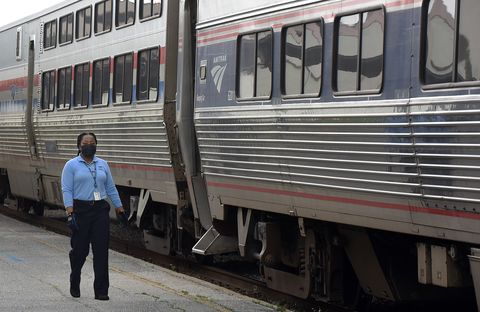 amtrak employee with face mask next to train