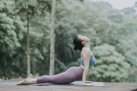 an asian chinese female yoga instructor demonstrating yoga poses cobra pose