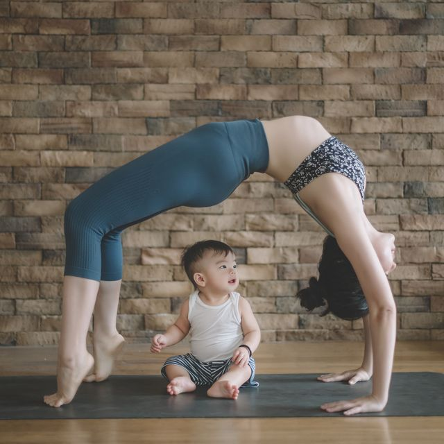 an asian chinese female yoga instructor with bridge pose while her son looking at her