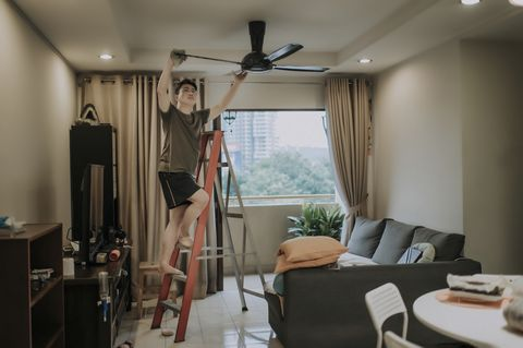 an asian chinese male cleaning ceiling fan at home