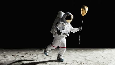 An astronaut on the moon holding a heart shaped helium balloon